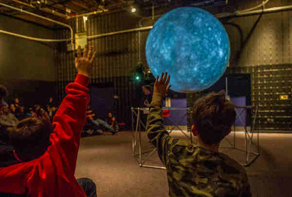"Two boys raise their hands at a ""Science on a Sphere"" presentation at the Goddard Visitor Center on Sunday, March 16, 2014. Image Credit: NASA Goddard / Bill Hrybyk"