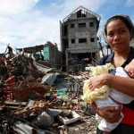 A woman and her baby amid debris and other destruction caused by Super Typhoon Haiyan in the Philippines. Photo: UNICEF / Jeoffrey Maitem