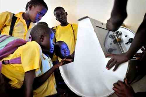 Children in Uganda gather around to use UNICEF's solar-powered Digital Drum, at Bosco Youth Centre in Gulu, northern Uganda.