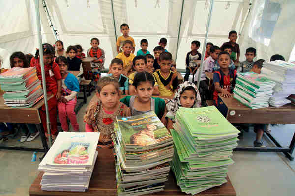 Students sit in front of new textbooks in one of 12 tented classrooms at Al Takiya Al Kasnazaniya camp for internally displaced persons in Karkh District, Baghdad Governorate, Iraq. Photo: UNICEF / Wathiq Khuzaie