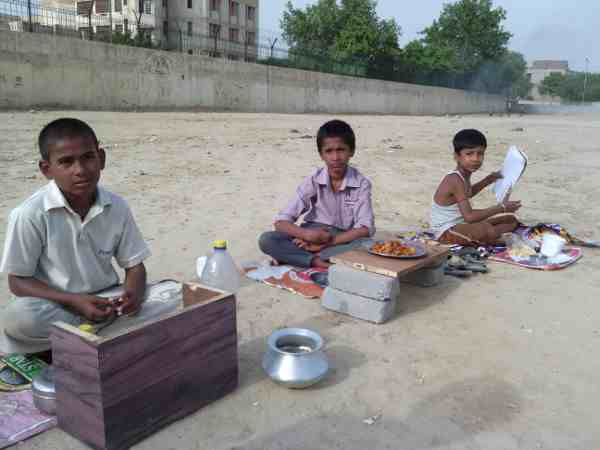 Young children forced by parents to sell eatables outside a school building in New Delhi, India. Photo: Rakesh Raman
