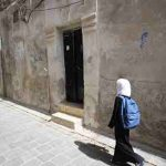 In eastern Aleppo, a young girl returns home from school.