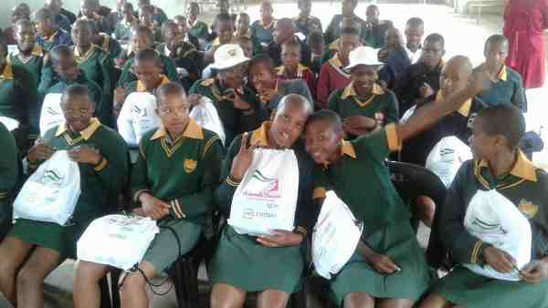 Care for Girls: Young girls pose with their free sanitary pads and school supplies.