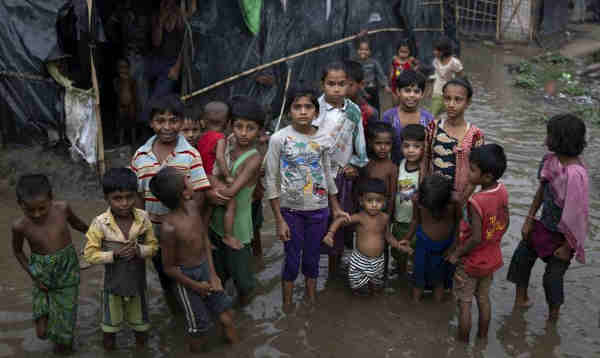 Rohingya refugee children wade through flood waters surrounding their families' shelters following an intense pre-monsoon wind and rain storm in Shamlapur Makeshift Settlement, Cox's Bazar district, Bangladesh on 20 May 2018. Photo: UNICEF