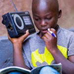 In Rwanda, a boy listens to a radio. Photo: UNICEF