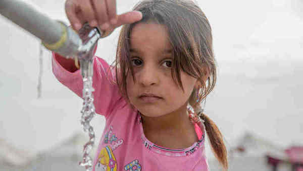 A young girl from Mosul takes water from a tap stand at a UNICEF-supported Temporary Learning Space in Hassan Sham Displacement Camp, Ninewa Governorate. Photo: UNICEF (Representational image)